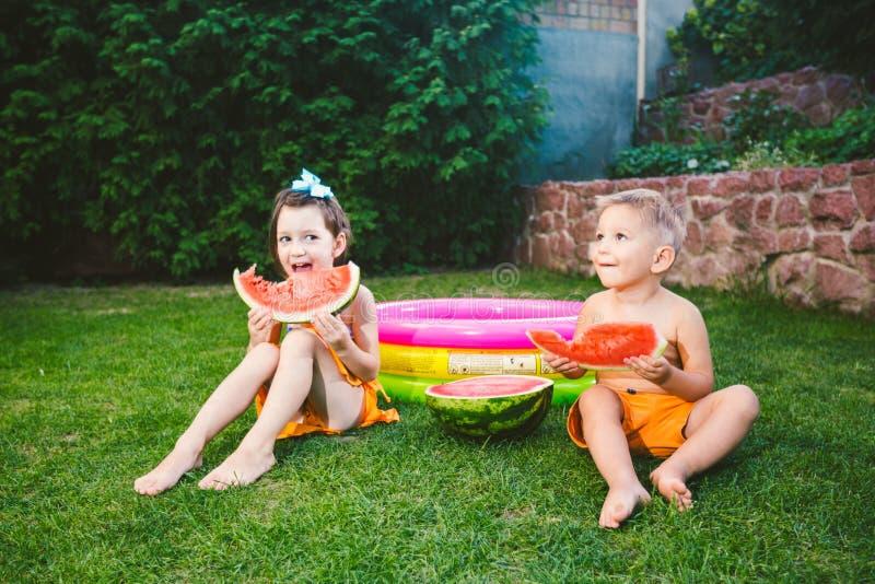 Lustiger Kleinkindbruder und -schwester, die zu Hause Wassermelone auf gr?nem Gras nahe aufblasbarem Pool im Yard isst Kleinkindj stockfotos