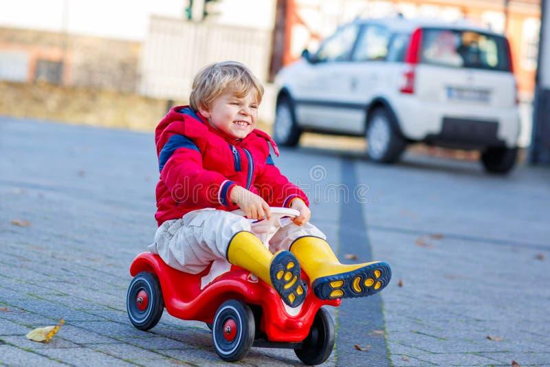 Lustiger Kleinkindjunge, der draußen Spielzeugauto fährt stockbild