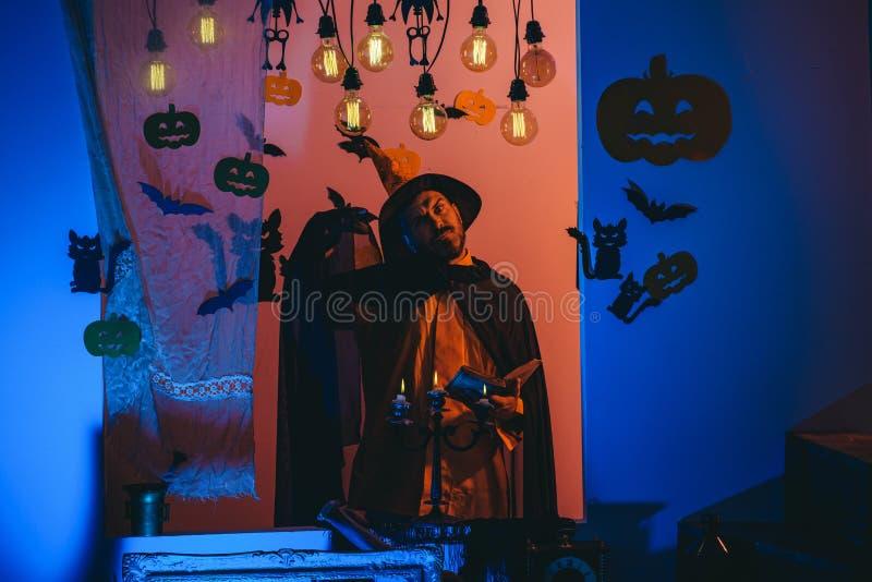 Lustiger kluger Zauberer auf einem Halloween-Hintergrund Furchtsamer Gesichtsmann mit Horror Make up K?rbishauptsteckfassungslate stockbilder