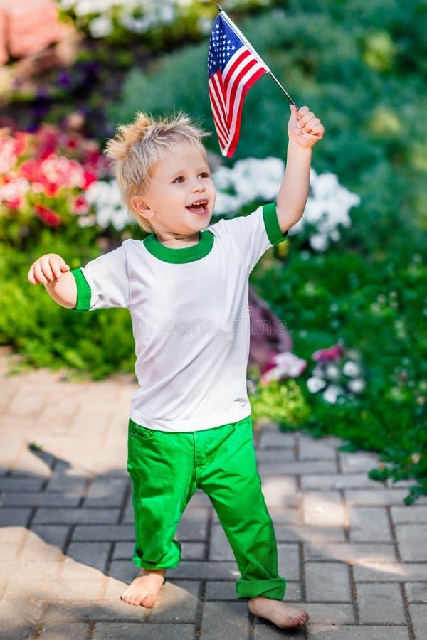 Lustiger lachender kleiner Junge mit dem blonden Haar, das amerikanische Flagge hält lizenzfreies stockbild