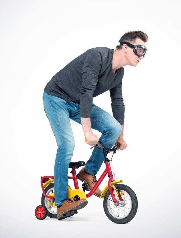 Lustiger Mann in den Schutzbrillen, in den Jeans und im schwarzen T-Shirt elt ein Fahrrad der Kinder rad lizenzfreies stockfoto