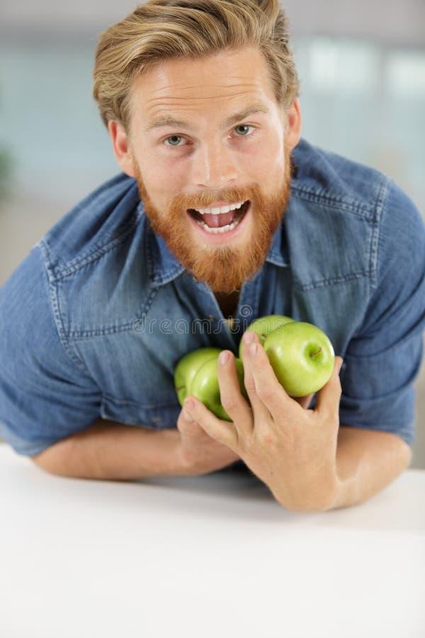 Lustiger Mann, der Äpfel hält lizenzfreies stockfoto