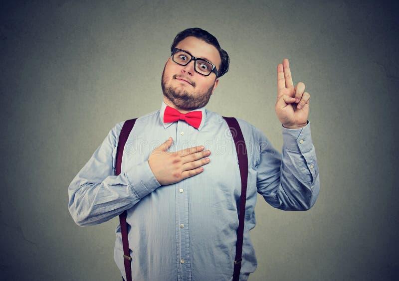 Lustiger Mann, der ausdrucksvoll Versprechen macht stockfotografie