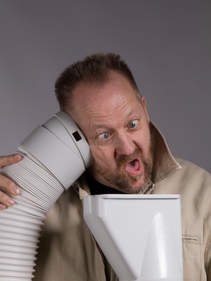 Lustiger Mann, der durch Rohr spricht lizenzfreie stockbilder