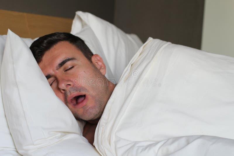 Lustiger Mann, der im Bett schnarcht stockfotografie