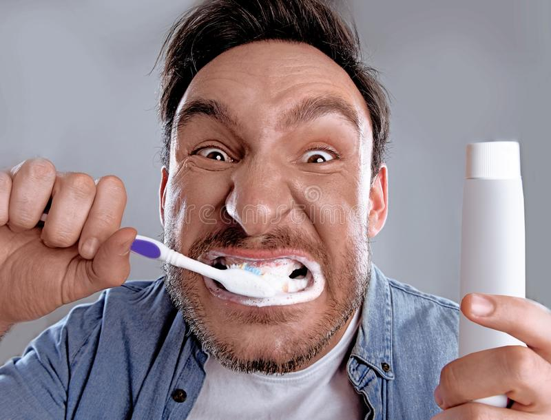 Lustiger Mann, der seine Zähne putzt lizenzfreie stockfotos
