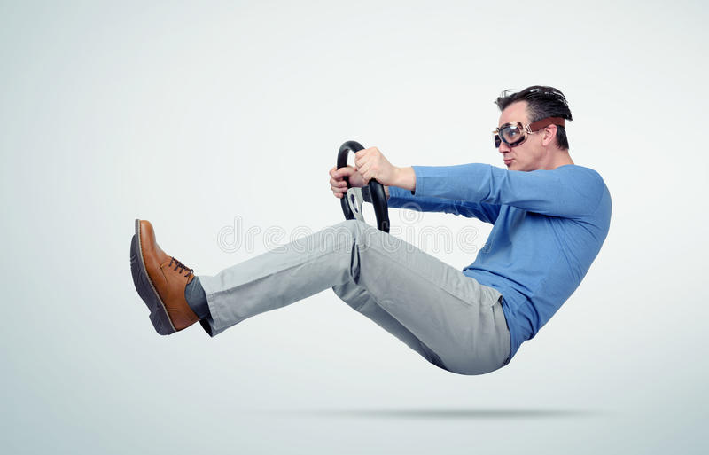 Lustiger Mann im blauen T-Shirt und in den Schutzbrillen fährt ein Auto mit Lenkrad stockfotos