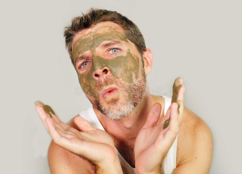 Lustiger Mann mit Gesichtsmaske der grünen Meerespflanze auf seinem Gesicht, das vor dem Spiegel verspottet auf unter Verwendung  lizenzfreie stockfotos