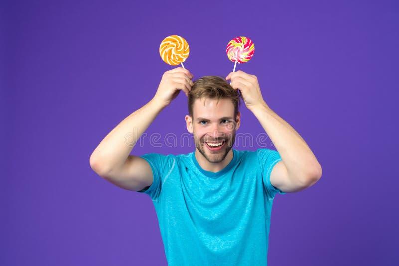 Lustiger Mann mit Lutschern auf Kopf auf violettem Hintergrund Macholächeln mit Süßigkeiten auf Stöcken auf purpurrotem Hintergru stockbilder