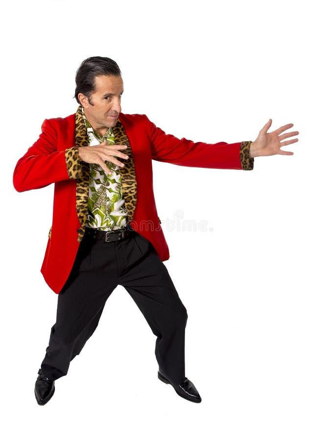 Lustiger Rührstangenplayboy und Mann des Bonvivanten reifer, der rote Kasino Jacke und Hawaiihemd steht glücklich trägt, Gigolo e lizenzfreie stockfotografie