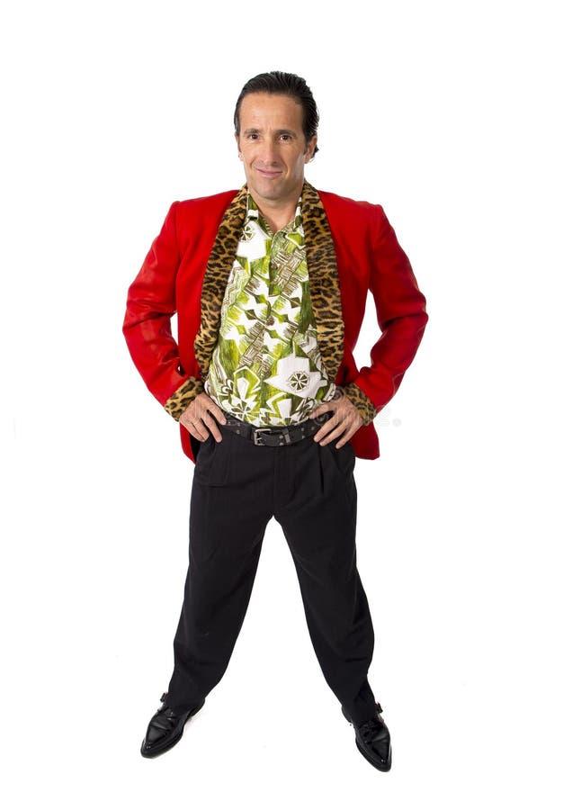 Lustiger Rührstangenplayboy und Mann des Bonvivanten reifer, der rote Kasino Jacke und Hawaiihemd steht glücklich trägt, Gigolo e stockbilder