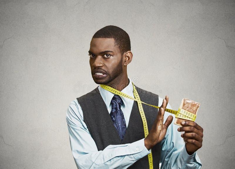 Lustiger schauender Mann, der, versucht süßes Plätzchen nicht zu essen lizenzfreie stockbilder