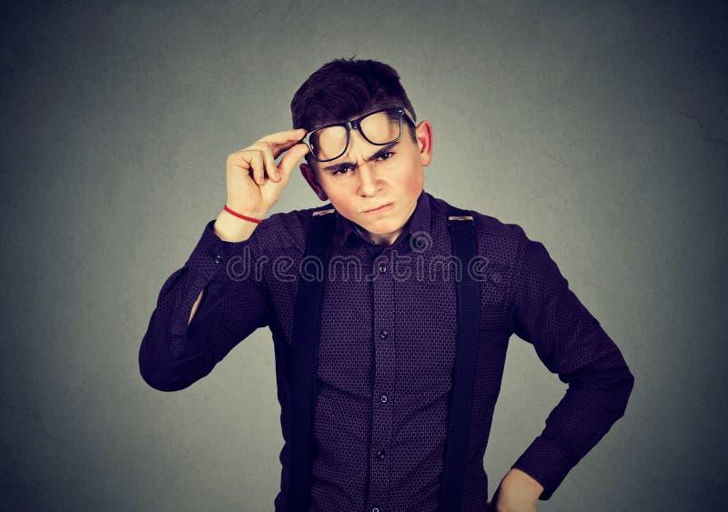 Lustiger schauender skeptischer mürrischer junger Mann in den Gläsern stockfoto
