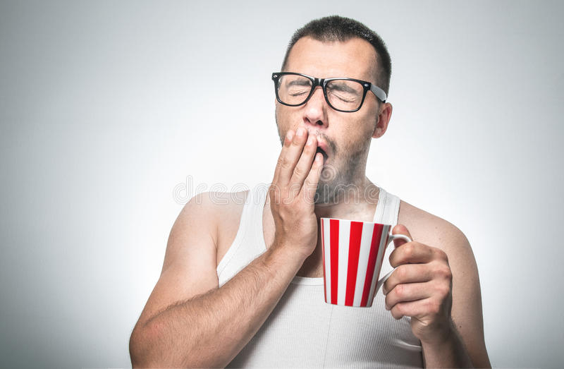 Lustiger schläfriger Mann mit Schalenkaffeegegähne lizenzfreie stockfotografie