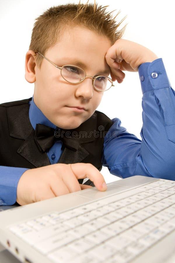 Lustiger Schulejunge mit dem Laptop getrennt auf Weiß lizenzfreies stockbild