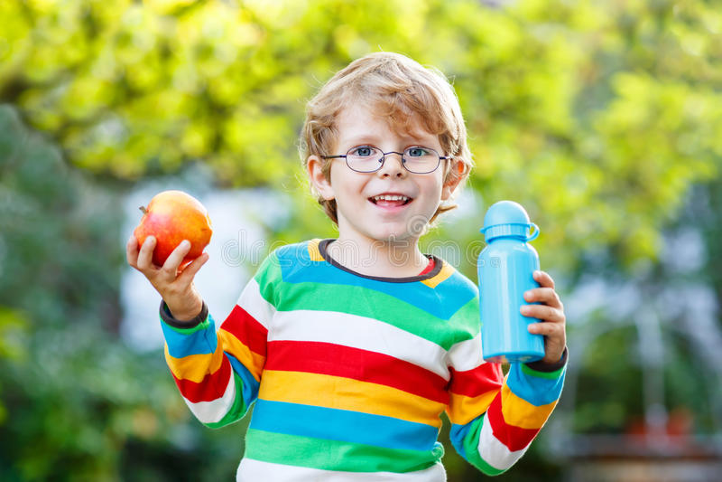Lustiger Schulkinderjunge mit Buch-, Apfel- und Getränkflasche lizenzfreies stockbild