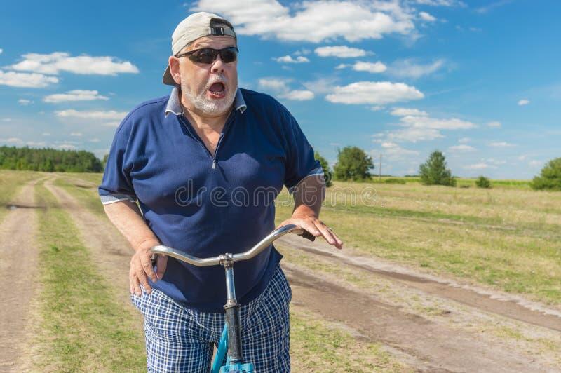 Lustiger Senior zeigt seine Furcht, um auf ein Fahrrad zu fahren stockbilder
