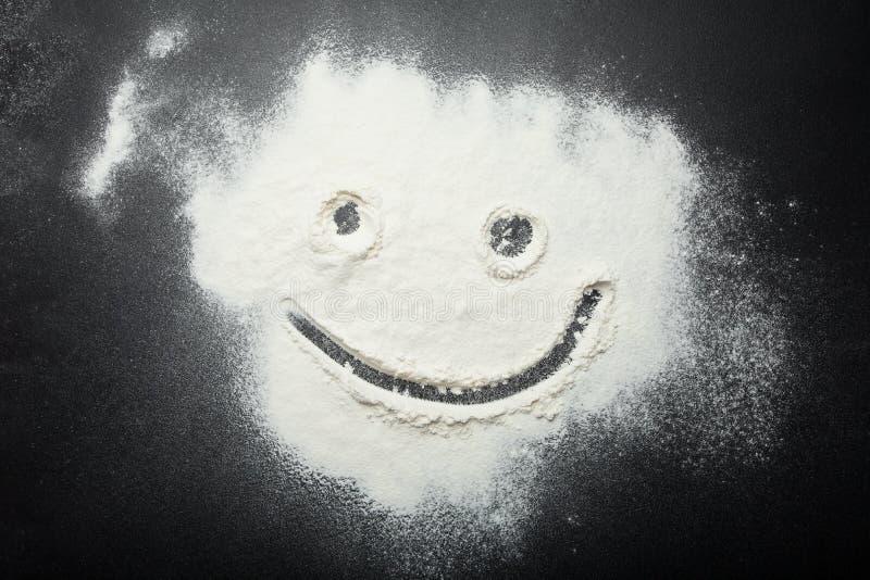 Lustiger smiley gemalt mit einem Finger auf dem Mehl stockbilder