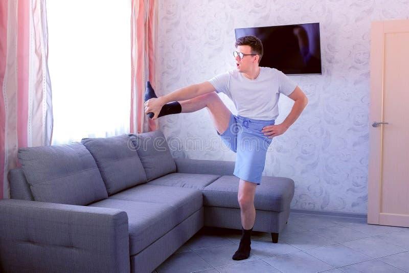 Lustiger Sonderlingsmann tut Vorwärtssteigungen und dehnt Übungen für Beine zu Hause aus Sportstimmungskonzept stockfotos