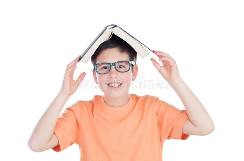 Lustiger Teenager von dreizehn mit einem Buch auf Kopf lizenzfreie stockfotografie
