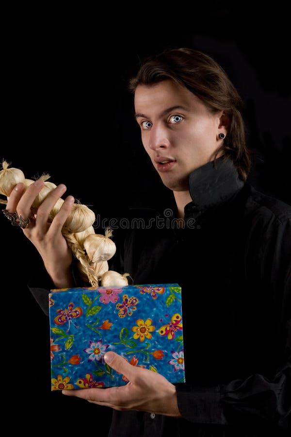 Lustiger Vampir mit dem Geschenkkasten, der Knoblauch herausnimmt stockfotos