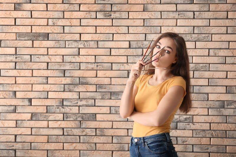 Lustiger weiblicher Künstler gegen Backsteinmauer lizenzfreie stockfotografie