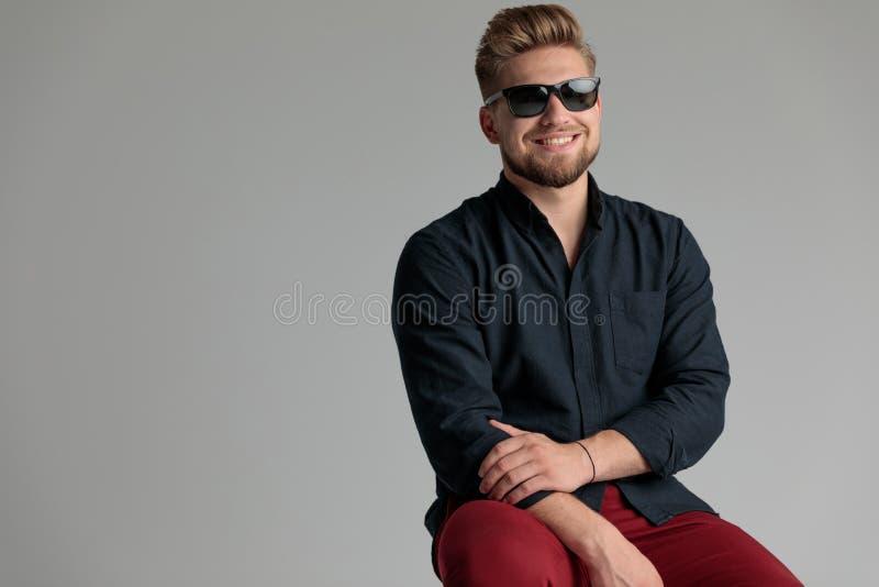 Lustiger zufälliger Mann, der seinen Arm lächelt und hält lizenzfreies stockbild
