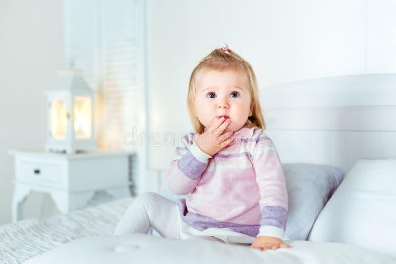 Lustiges überraschtes blondes kleines Mädchen, das auf Bett im Schlafzimmer sitzt stockfotos