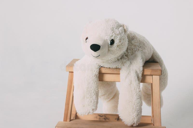 Lustiges altes weißes Eisbärspielzeug auf dem Holzstuhl lokalisiert auf grauem Hintergrund stockfotos