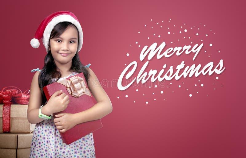 Lustiges asiatisches Kind, das roten Hut Sankt mit Weihnachtsgeschenk trägt stockbild