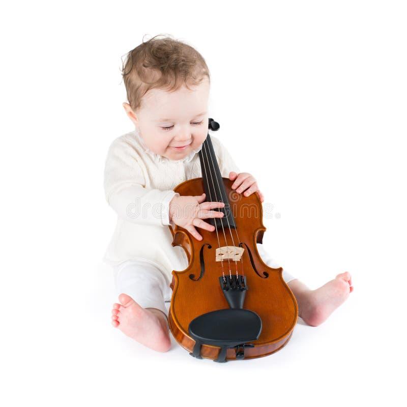 Lustiges Baby, das mit einer großen Violine spielt stockbild