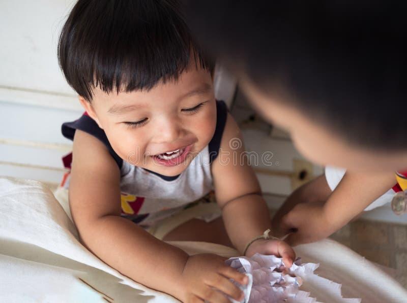 Lustiges Baby genießen, ein Stückpapier zusammen zu spielen stockfotografie