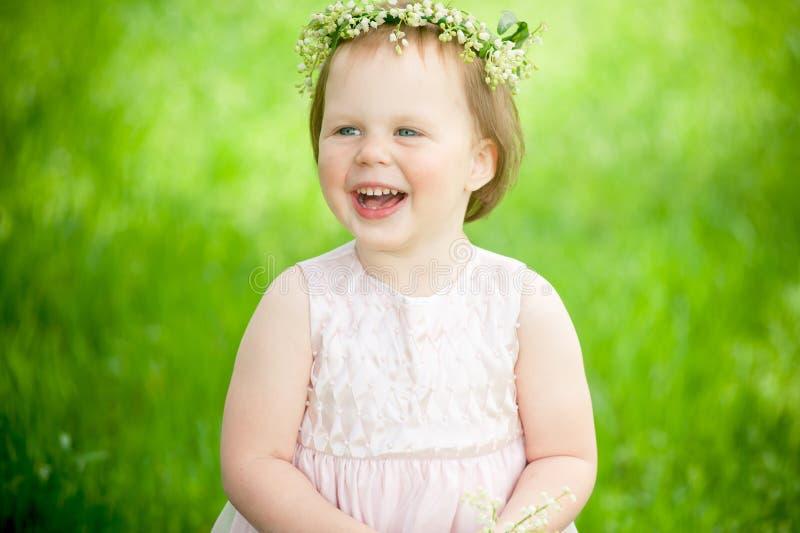 Lustiges Baby im Kranz des Lilienlächelns stockbild