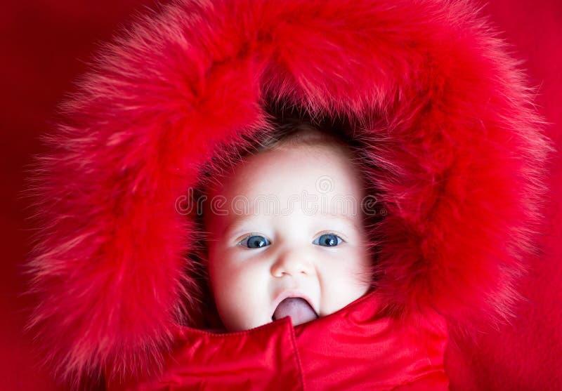 Lustiges Baby mit blauen Augen in der warmen Wintersteckfassung stockbild