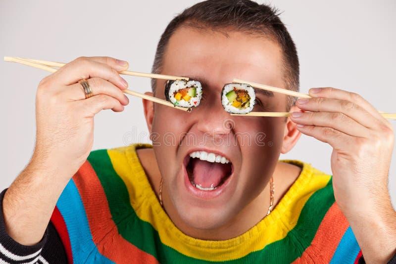 Lustiges Bild des Mannes mit Sushi stockbild