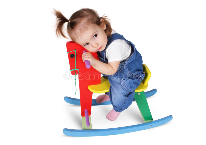 Lustiges durchdachtes Kind träumt auf dem Spielzeugpferd, lokalisiert auf Weiß lizenzfreies stockbild