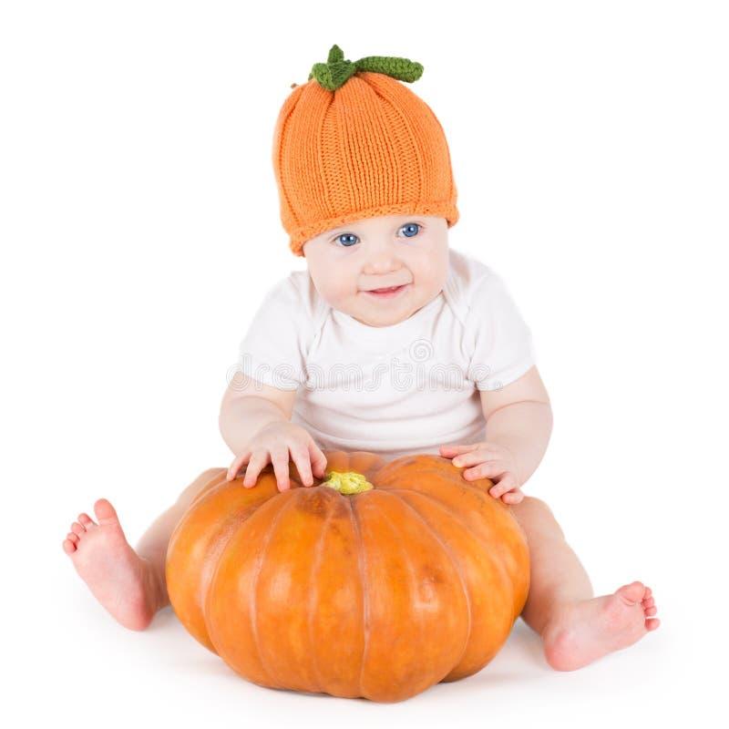 Lustiges entzückendes kleines Baby, das mit großem Kürbis spielt lizenzfreie stockbilder