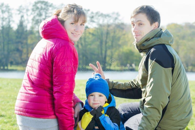 Lustiges Familienporträt von den Eltern, die Häschenohren Sohn vorlegen lizenzfreie stockfotos