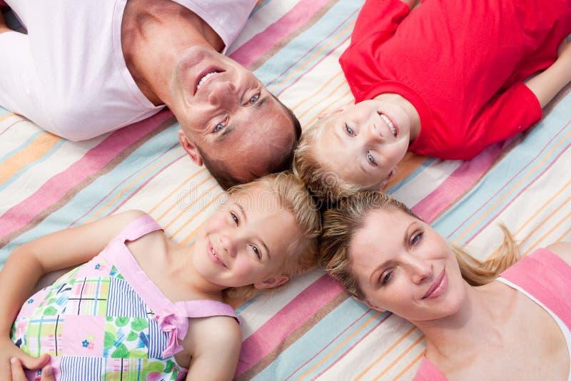 Lustiges Familienschlafenlügen auf dem Gras stockfoto