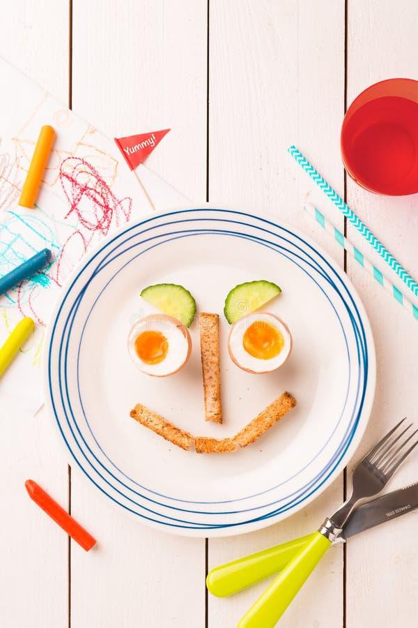 Lustiges Gesicht - das Frühstück des Kindes - Eier, Toast und Gurke lizenzfreies stockbild
