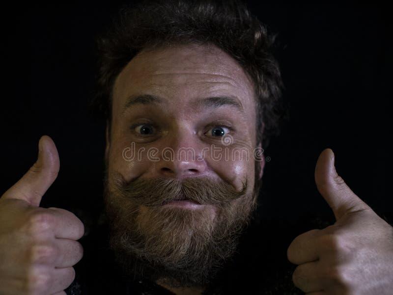 Lustiges Gesicht eines Mannes mit einem Bart- und Schnurrbartabschlu? oben und Daumen zeigend stockbilder
