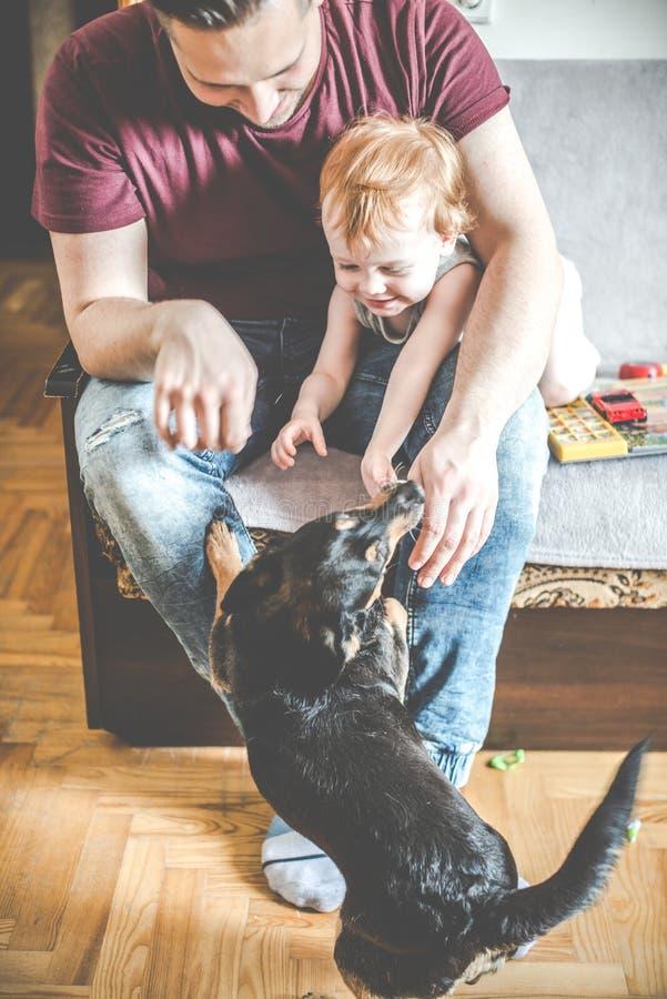 Lustiges glückliches Moment-, Vati- und Sohnspiel mit Hund lizenzfreie stockbilder