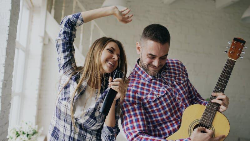 Lustiges glückliches und liebevolles Paartanzen und spielen Gitarre Mann und Frau haben Spaß während ihres Feiertags zu Hause stockfoto