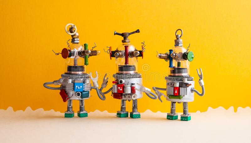 Lustiges Glas ging UFO-Roboter auf einer fantastischen Landschaft voran Drei humanoid Spielzeugroboter stehen in Verbindung Gelbe stockfotografie