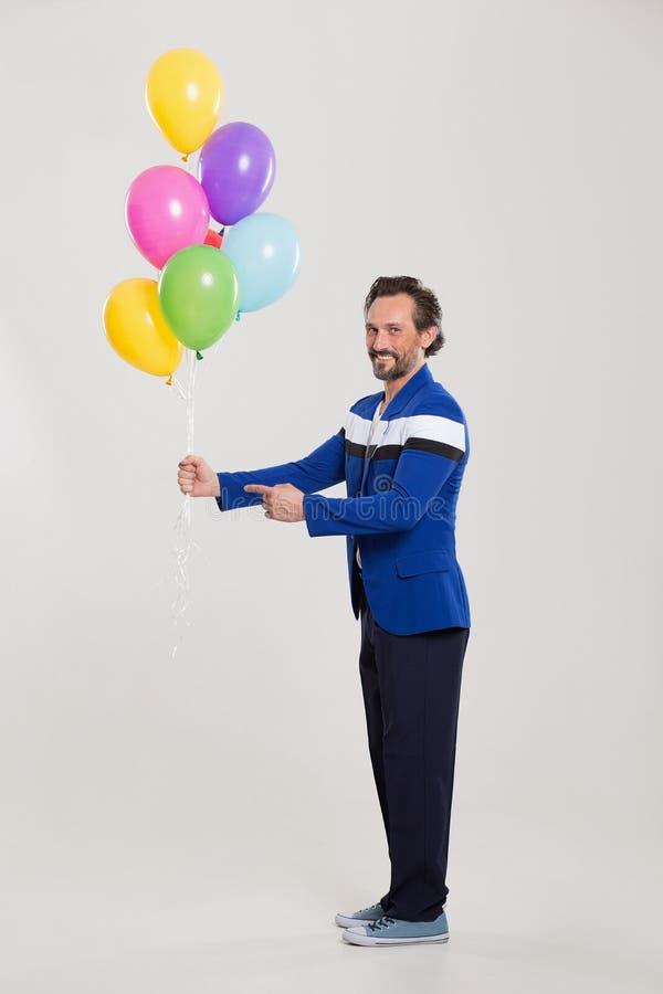 Lustiges harlecuin mit Ballonen lizenzfreies stockbild