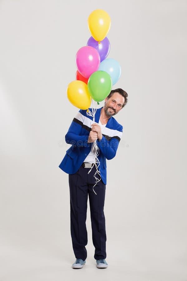 Lustiges harlecuin mit Ballonen stockfotos