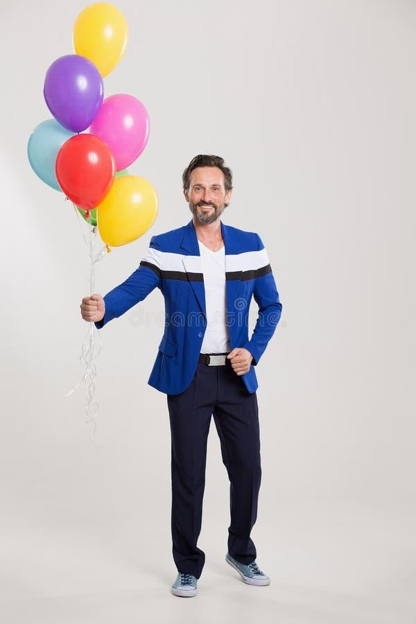 Lustiges harlecuin mit Ballonen lizenzfreie stockfotografie