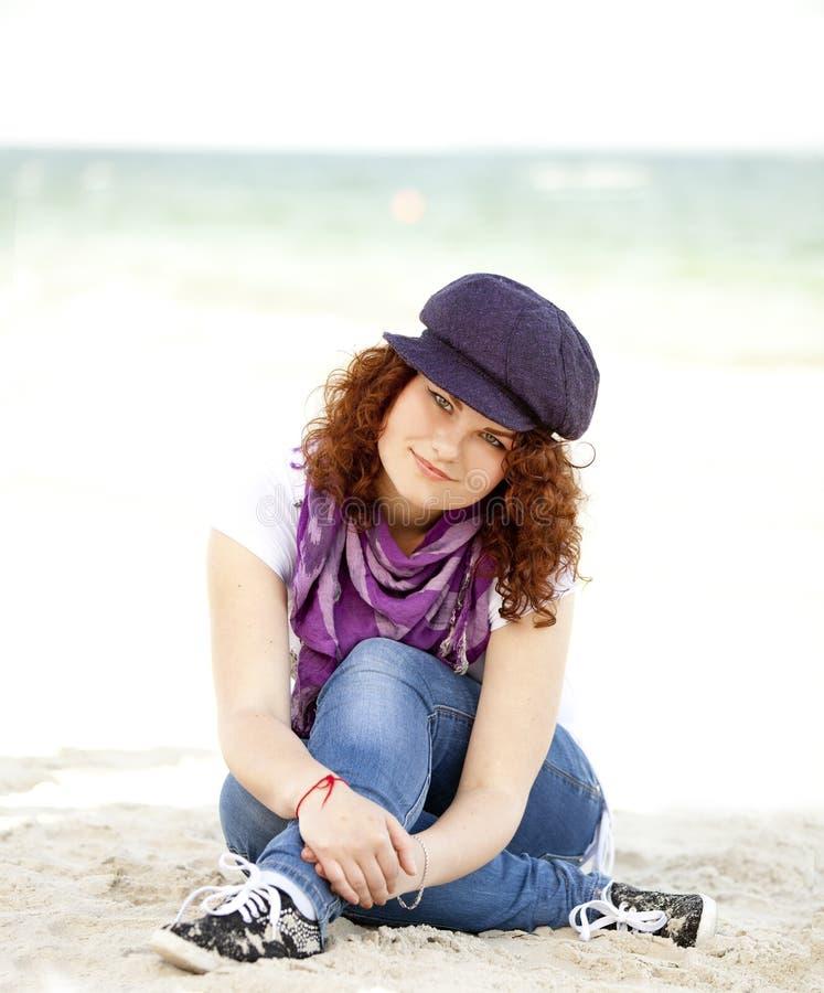 Lustiges jugendlich Mädchen, das auf dem Sand am Strand sitzt. lizenzfreie stockfotografie