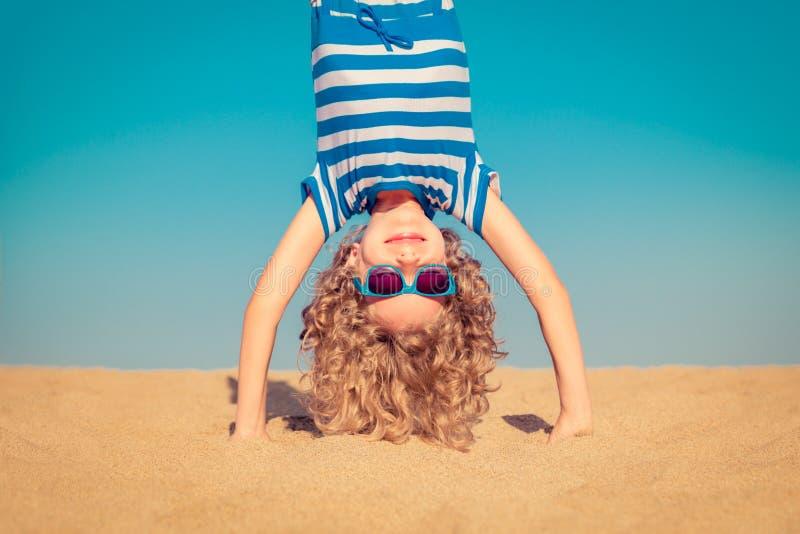 Lustiges Kind, das auf sandigem Strand umgedreht steht stockbilder