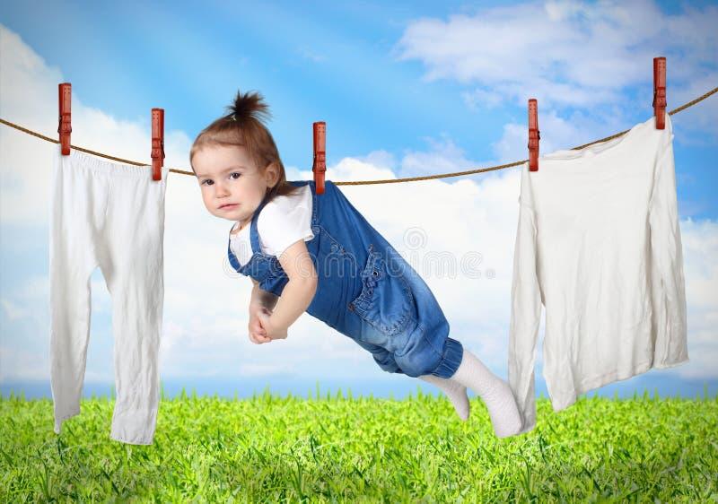 Lustiges Kind, das an der Linie mit Kleidung, Wäscherei kreatives conce hängt lizenzfreie stockbilder
